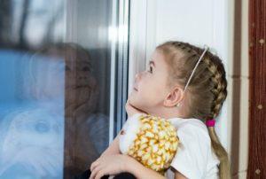 meisje met pop zit voor een raam en kijkt met verwachtingsvolle blik naar boven. je ziet haar weerspiegeling in het raam